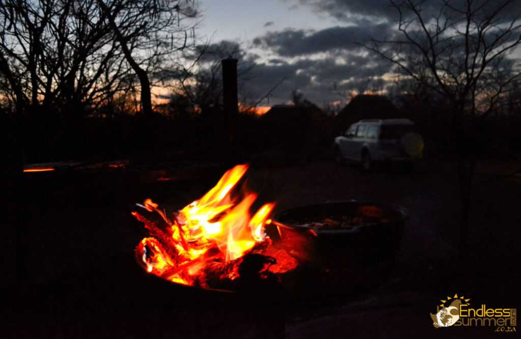 Campfire and braai burning in the Kruger Park with the sun setting